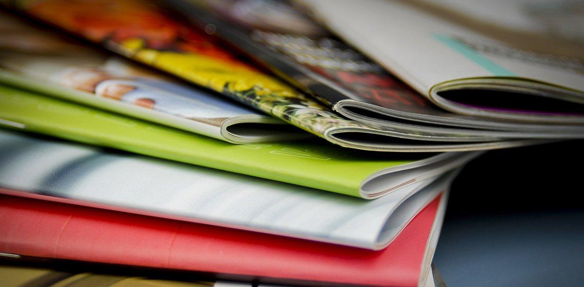 Viele mehrfarbige Broschüren liegen übereinander auf dem Tisch