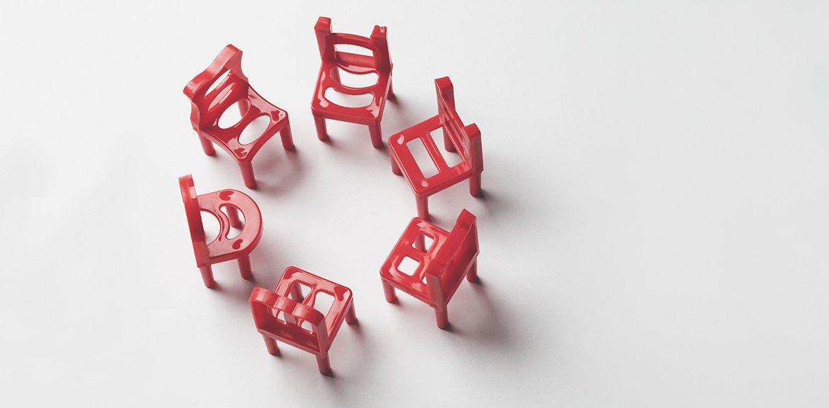 Rote Stühle in einem Kreis auf einem hellgrauen Hintergrung