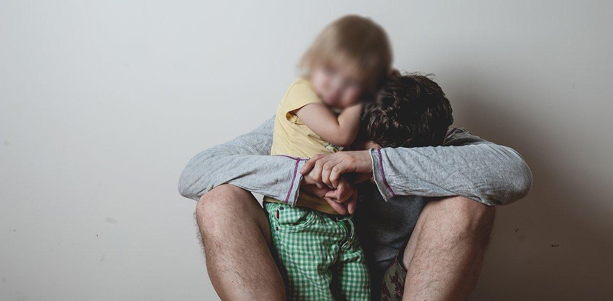 Alkoholisierter Vater, der ein kleines saueres Kind umarmt