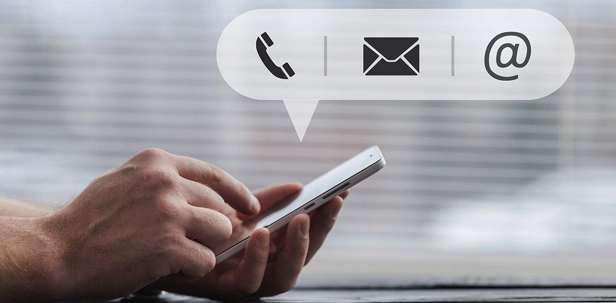 Eine Hand hält ein Handy und die andere tippt darauf. Oben darüber werden die Symbole für Telefon, Nachricht und E-Mail eingeblendet.