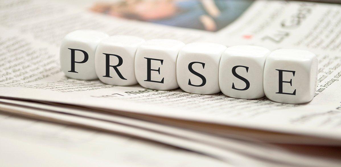 Kleine Würfel, auf denen das Wort Presse steht, liegen auf einer Zeitung