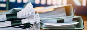 Unterlagen und Ordner, die auf dem Tisch liegen