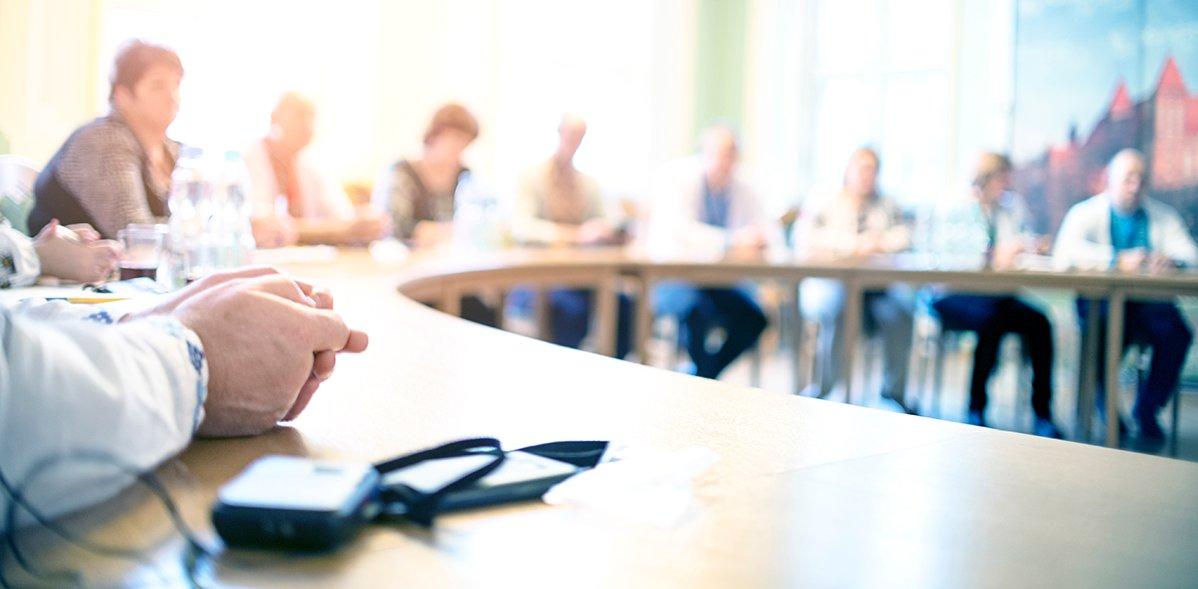 Menschen an einem runden Tisch diskutieren über verschiedene Themen