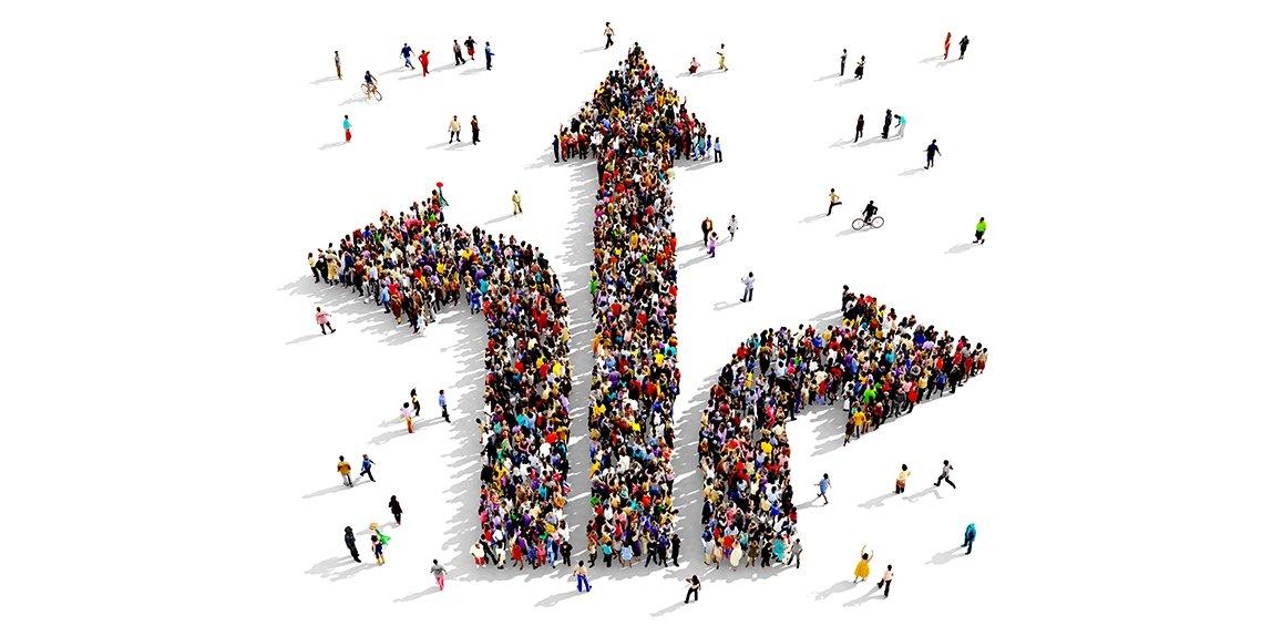 Große und vielfältige Gruppe von Menschen, die von oben gesehen werden, versammelt sich in Form von Richtungspfeilen