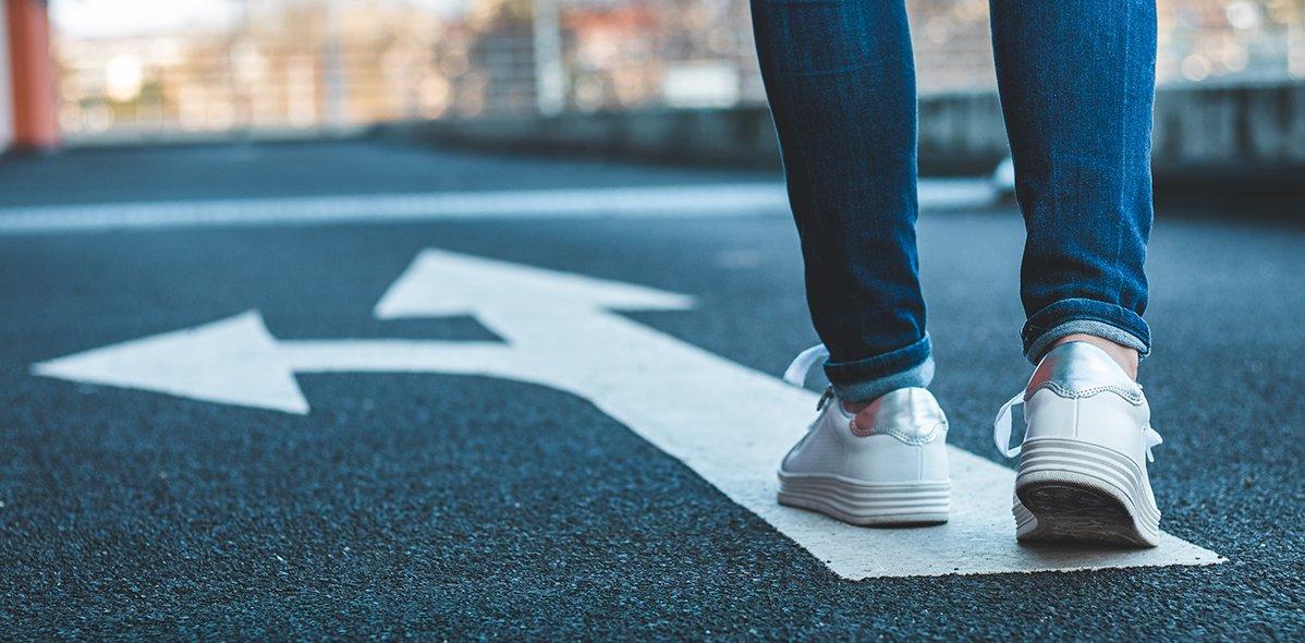 Weibliche Beine, die auf einer Asphaltstraße auf einem Richtungsschild stehen