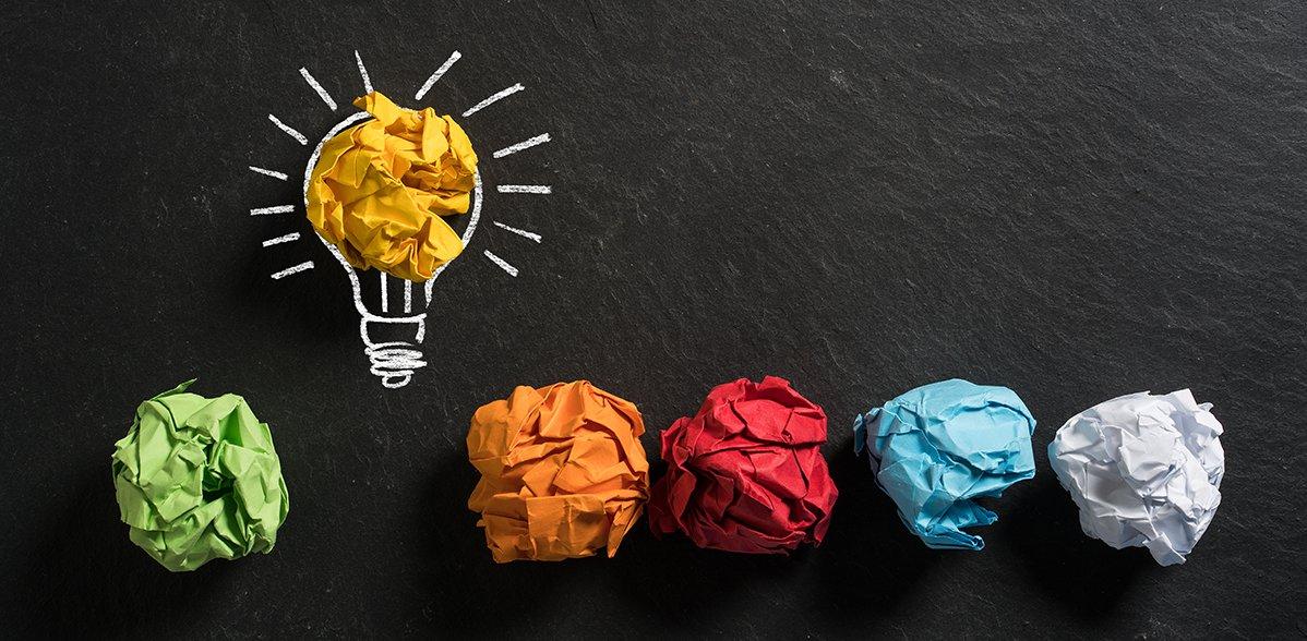 Zerknüllte farbige Papierbälle, die in einer Reihe liegen. Oben darüber ist ein Ball in einer mit Kreide gemalter Glühbirne