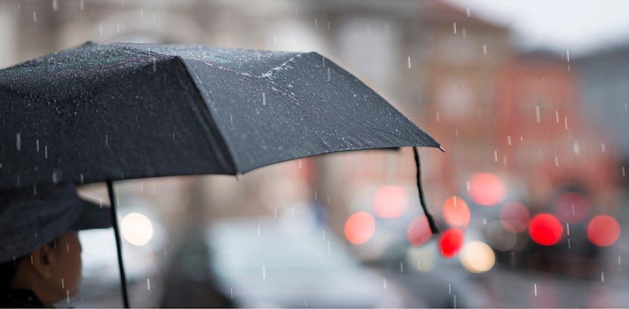 Ausschnitt einer Frau mit einem schwarzen Regenschirm, der Hintergrund ist unscharf dargestellt mit roten Blindpunkten