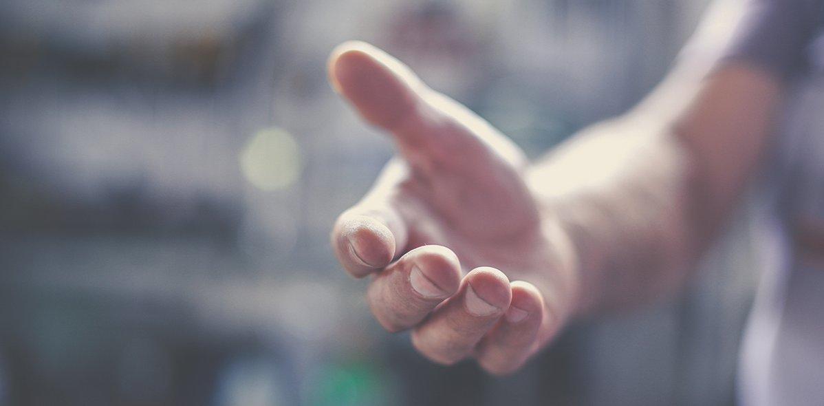 Eine ausgestreckte Hand eines Mannes, der Hintergrund ist verschwommen dargestellt