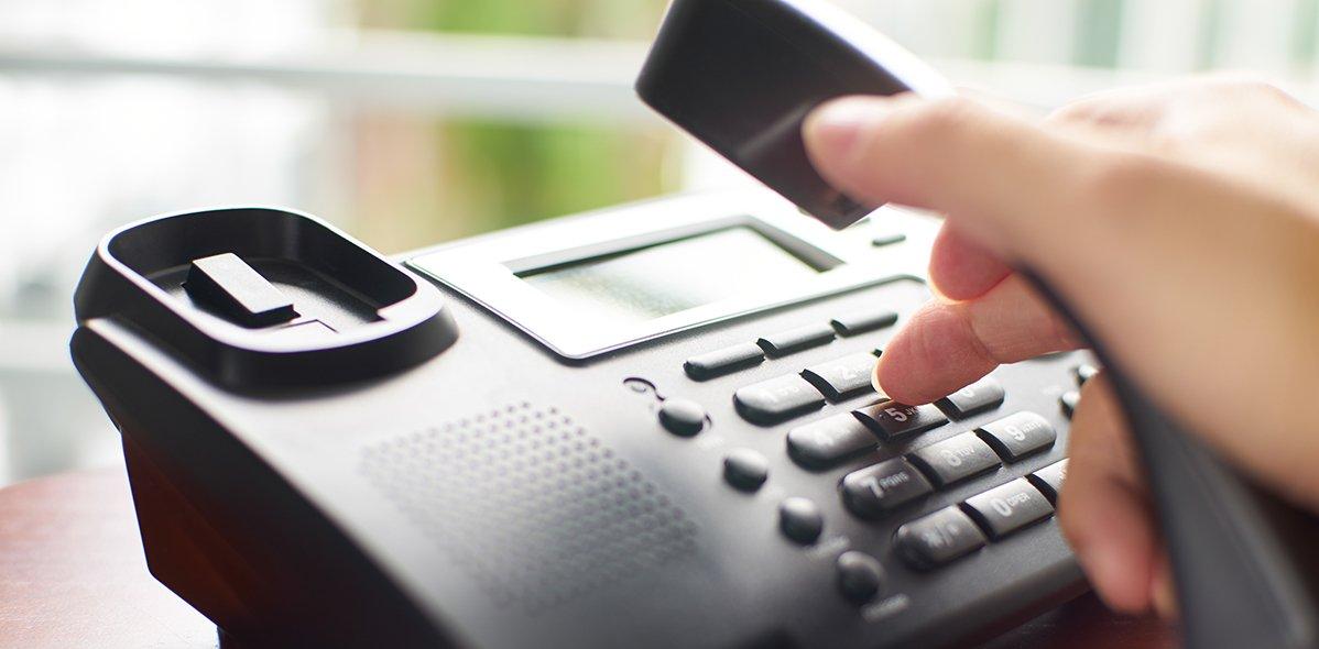 Eine Hand hält den Telefonhörer und drückt auf die Telefontasten
