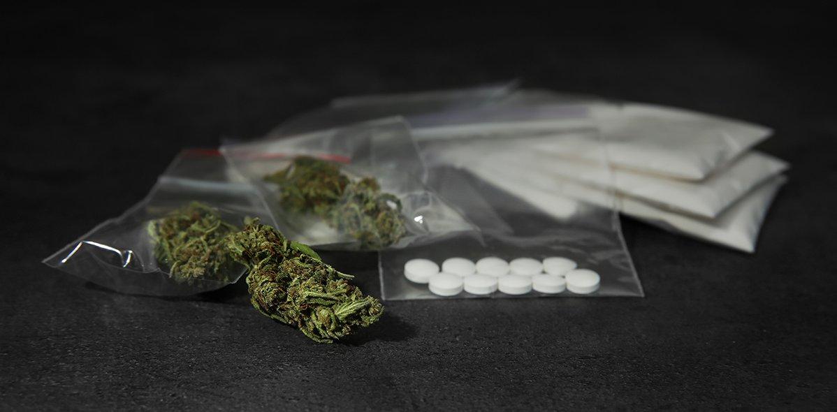Unterschiedliche illegale Drogen auf einem grauen Tisch