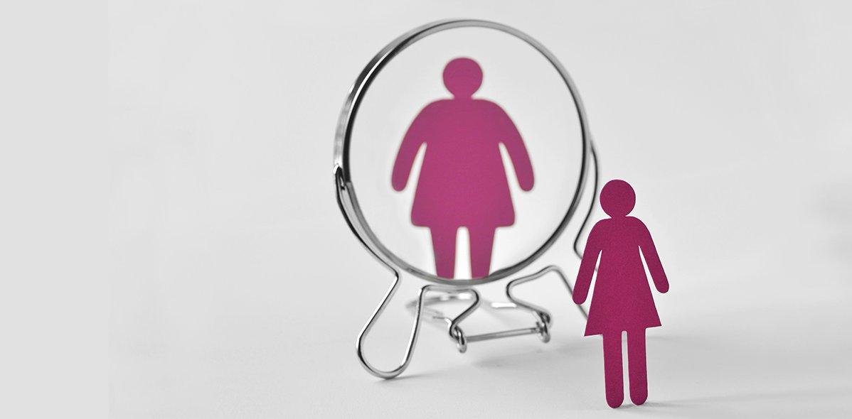 Pappfrau, die in den Spiegel schaut und sich selbst als dicke Frau sieht