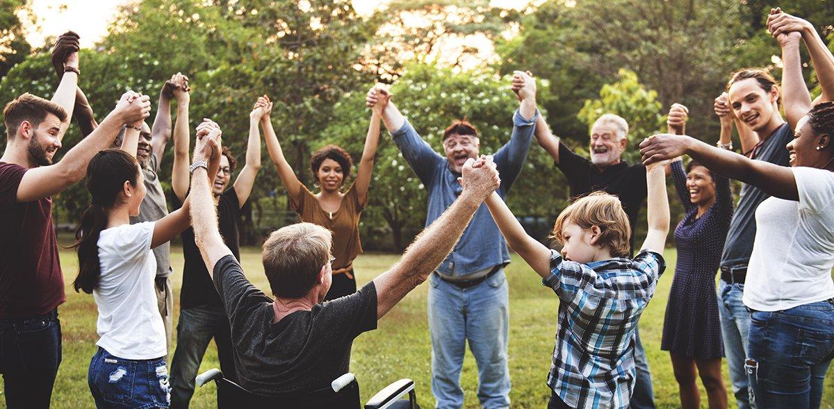 Gruppe von Menschen, die im Park die Hände zusammen hochhalten