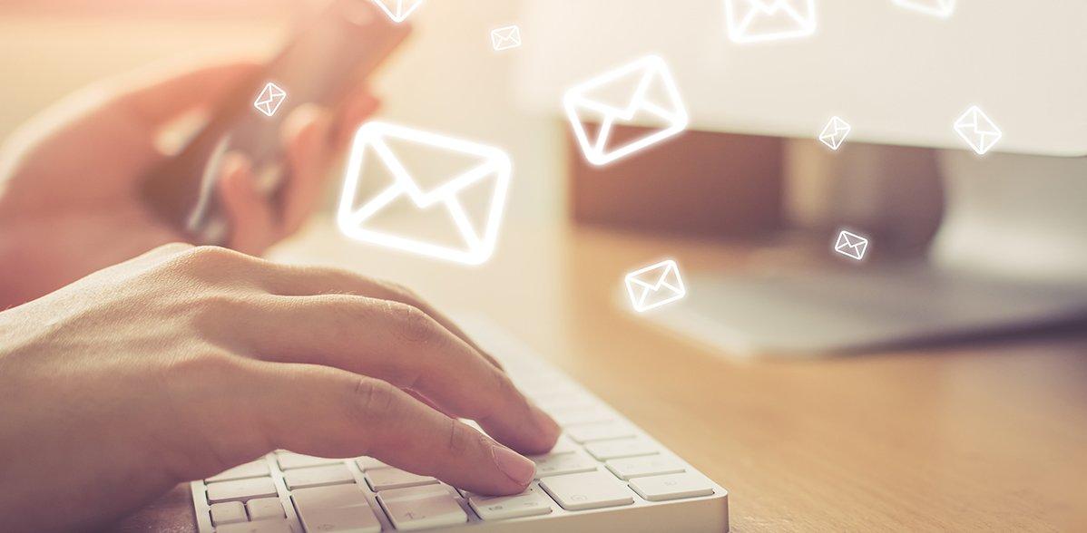 Eine Hand, die auf einer Tastatur tippt und mit der anderen einen USB-Stick hält. Nach oben fliegen zahlreiche E-Mail-Symbole.