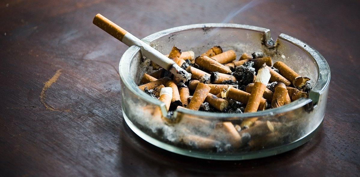 Aschenbecher mit einer angezündeten Zigarette
