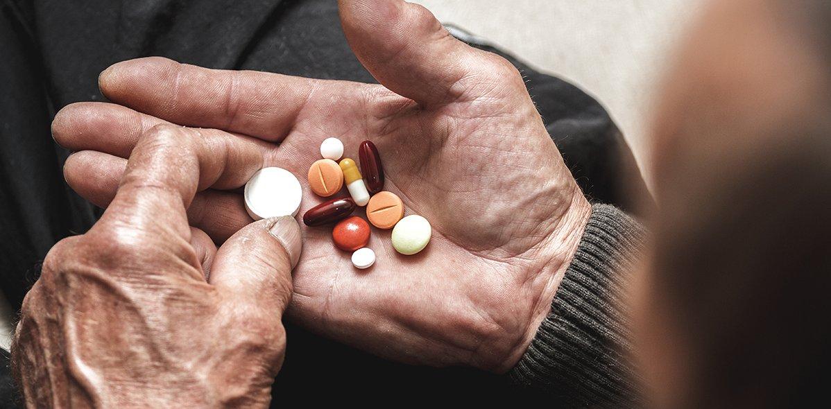 Viele mehrfarbige Tabletten in den Händen eines älteren Mannes